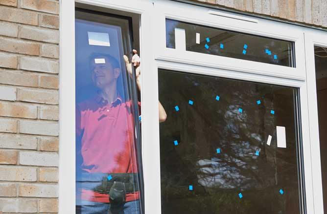 Man with drill repairing double glazing